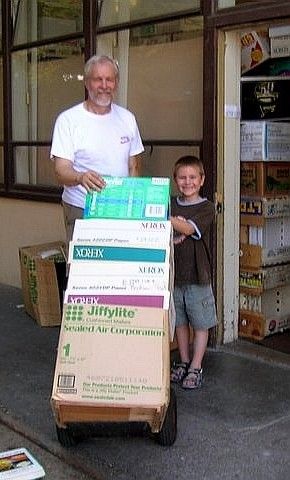 Father and son moving boxes of books stacked on a dolly