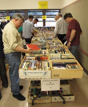 Customers examining books for sale at a table