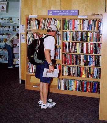 person looking at books on a shelf